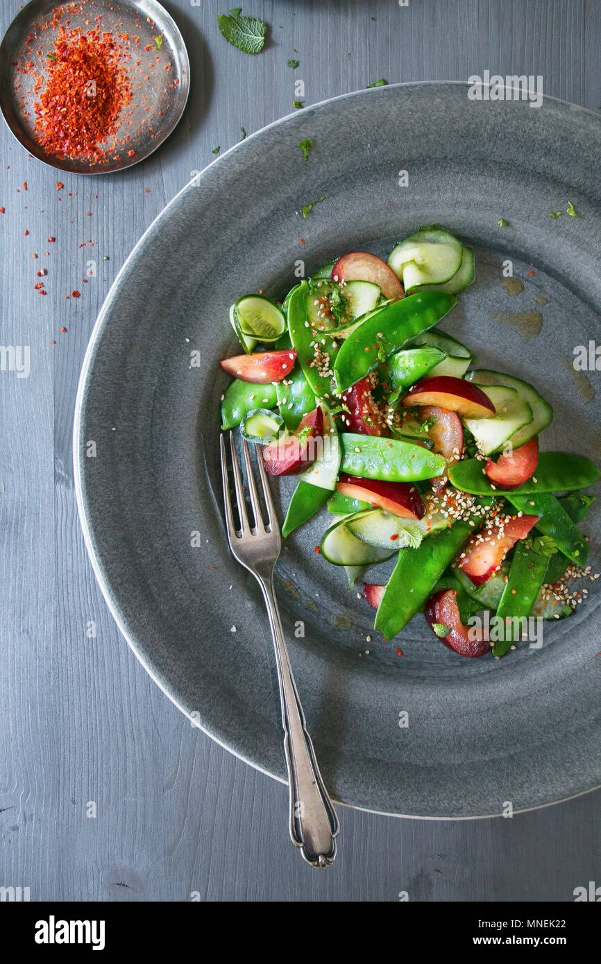 Sugar snap salad with plums - Stock Image