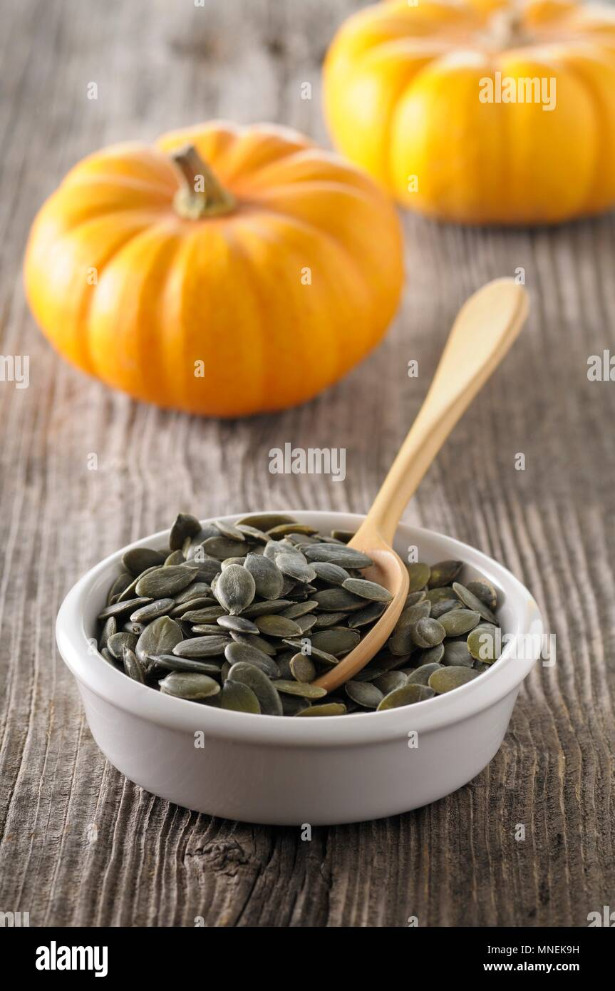 A dish of pumpkin seeds with a spoon - Stock Image