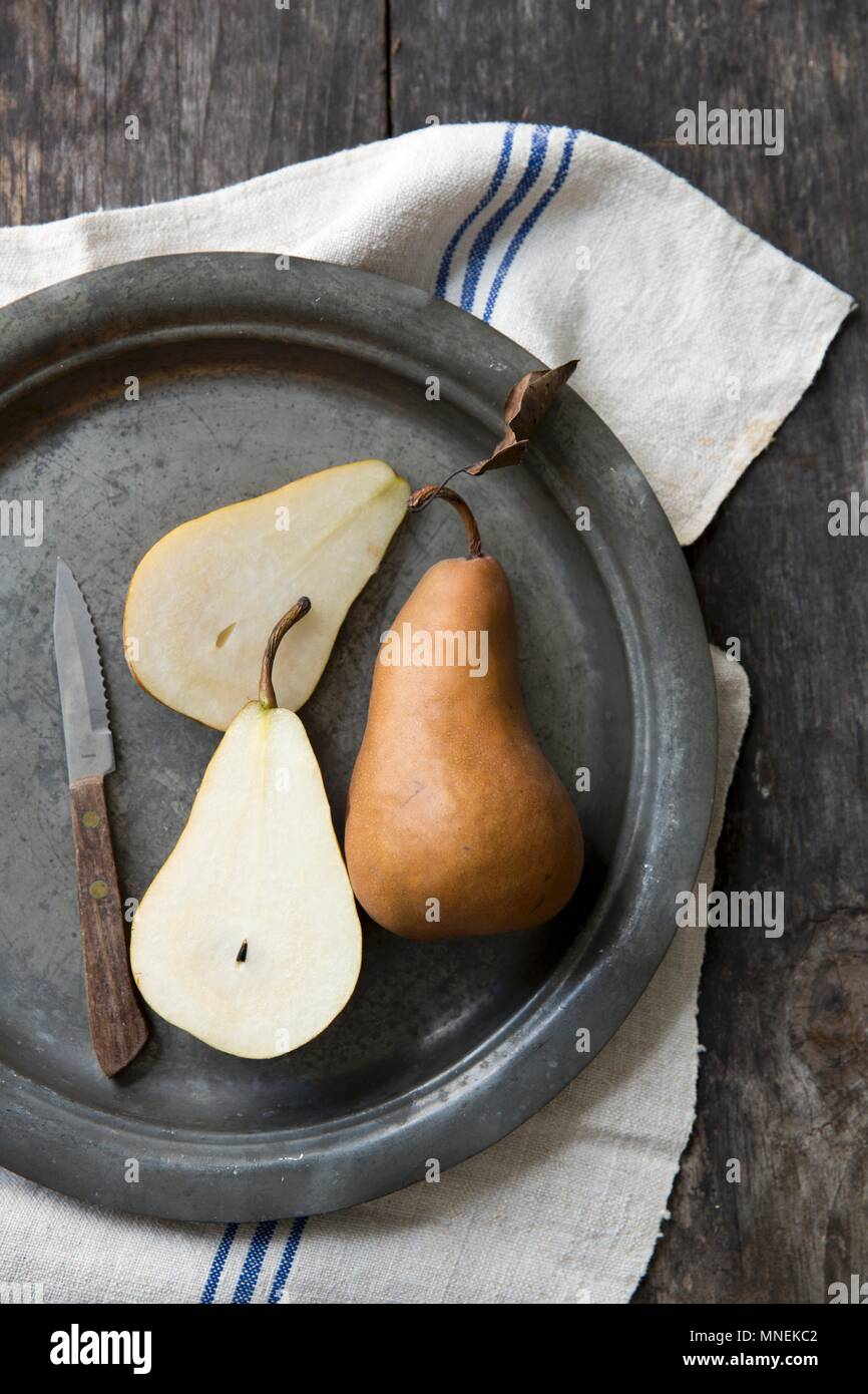 Boskop pears, whole and halved, on a pewter plate - Stock Image
