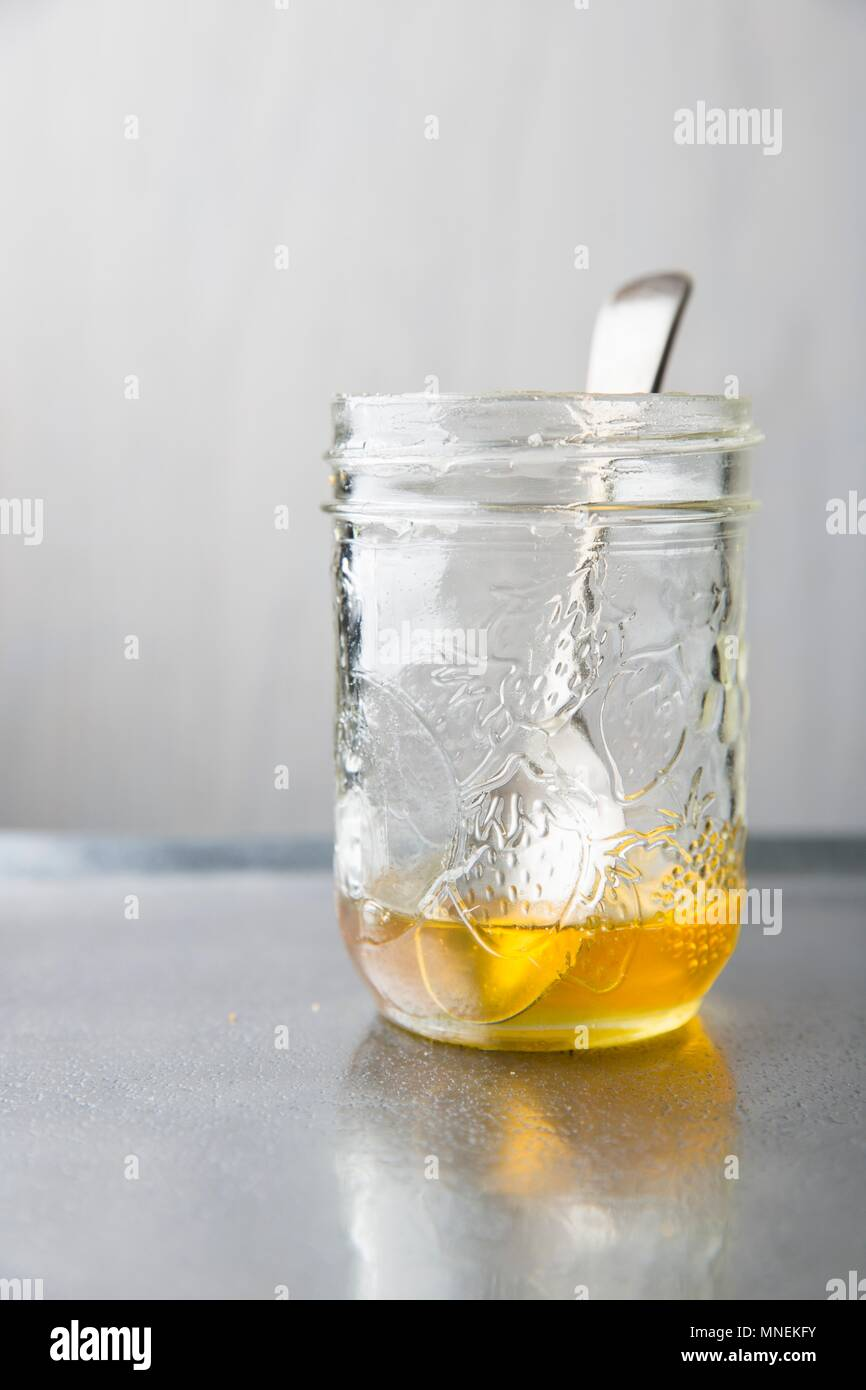 Honey in preserving jar with a spoon on a metal tray - Stock Image