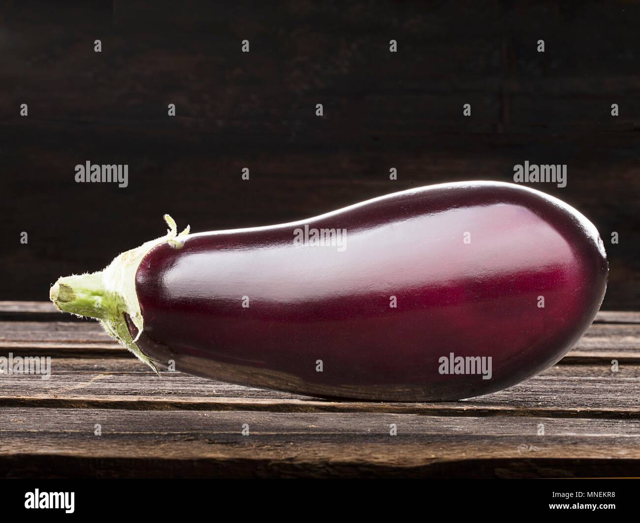 An eggplant on a wooden background - Stock Image