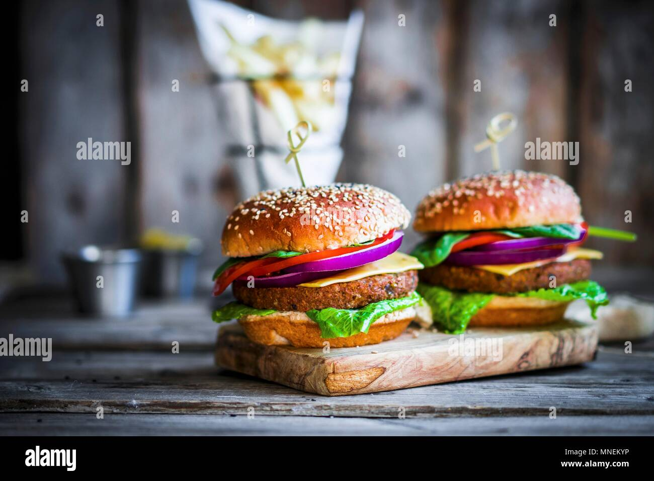 Homemade burgers on rustic wooden surface - Stock Image