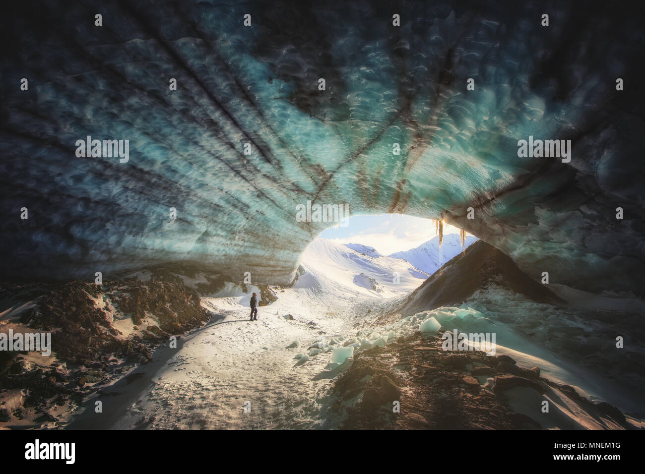Ice cave sunset hiker hiking frozen blue Yukon Canada snow mountains glacier - Stock Image