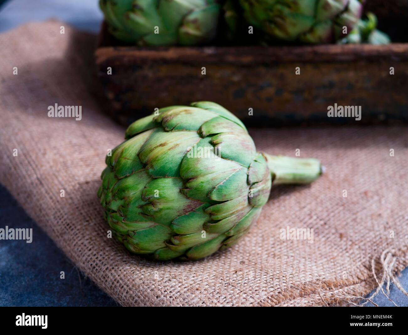 Fresh artichoke on sackcloth - Stock Image
