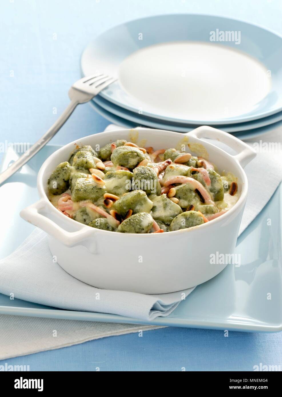 Gratinated spinach gnocchi in a creamy cheese sauce - Stock Image