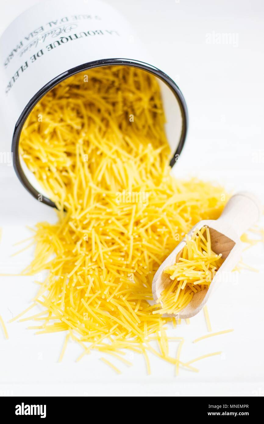 Angel hair pasta falling out of an overturned enamel bucket - Stock Image