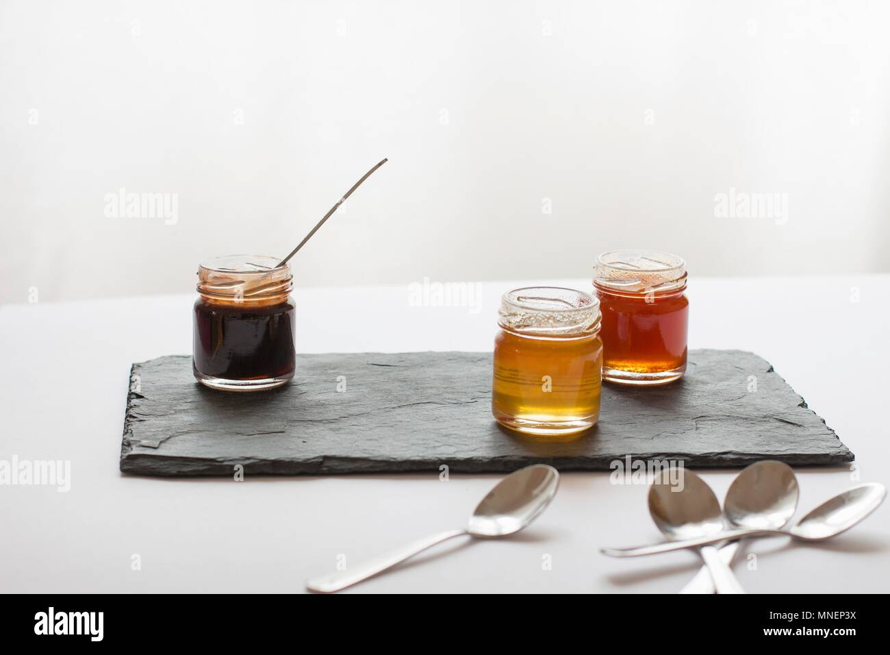 Various jars of honey on a slate platter - Stock Image