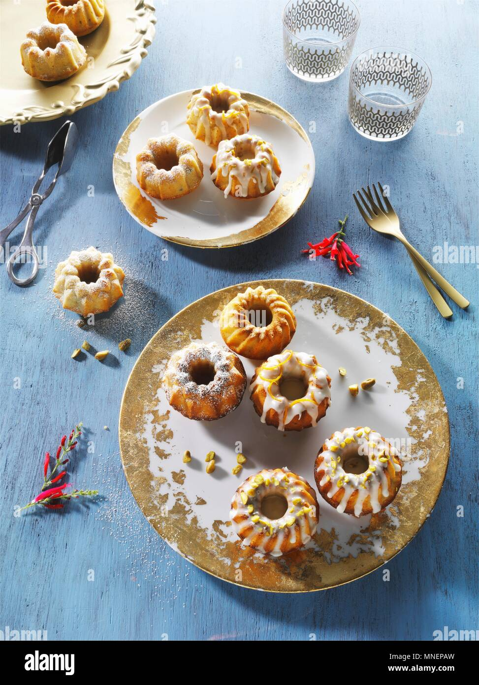 Mini Bundt cakes on gold-patterned plates on a blue wooden surface - Stock Image