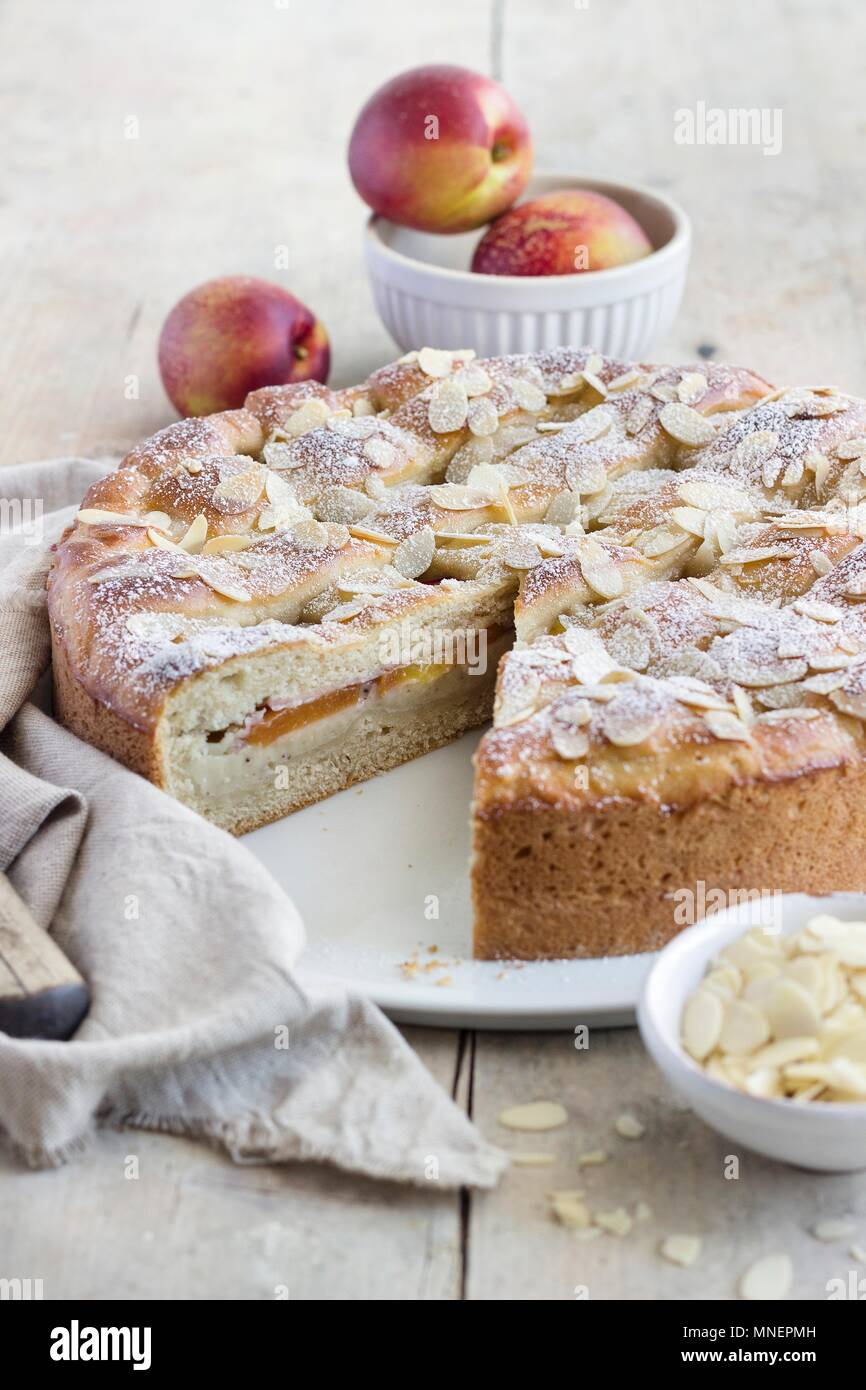 A summery nectarine cake made from quark oil dough and filled with vanilla pudding - Stock Image
