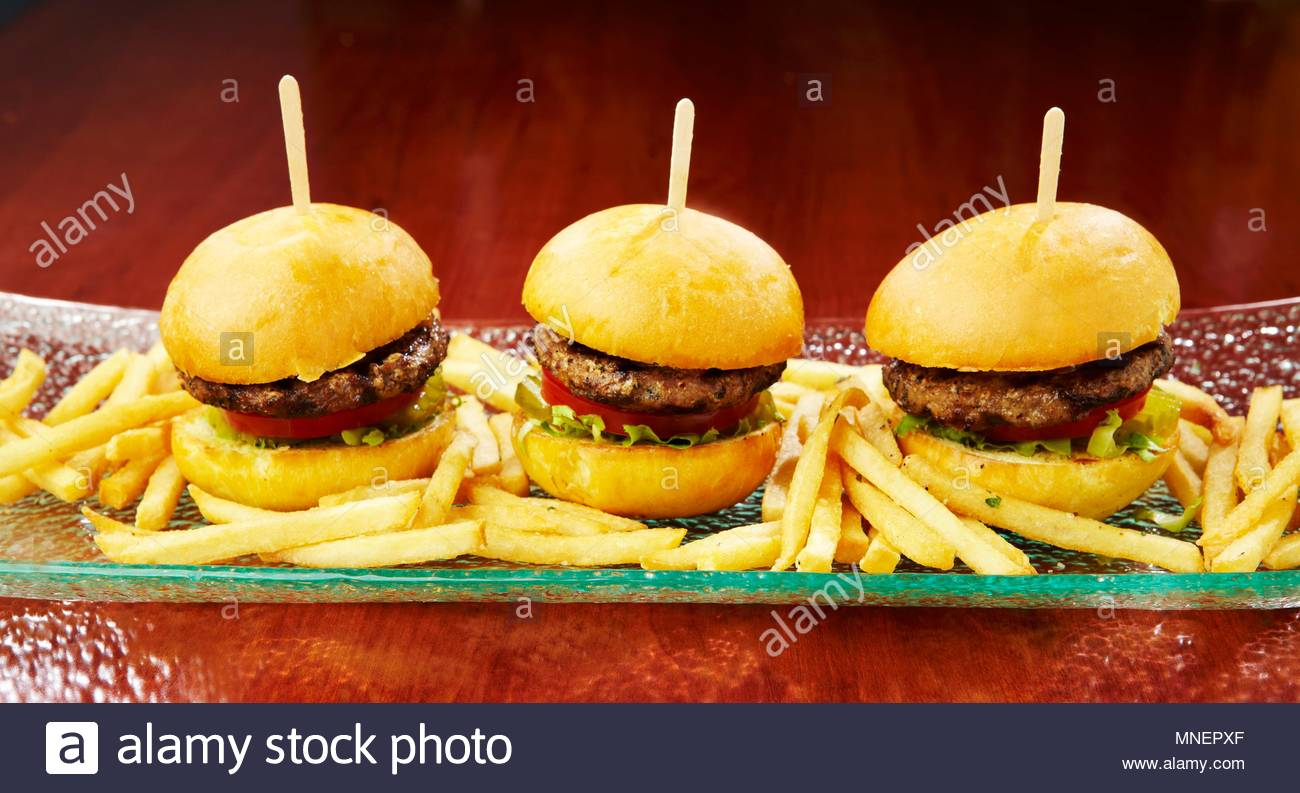 Three mini burgers with chips on a long serving platter - Stock Image