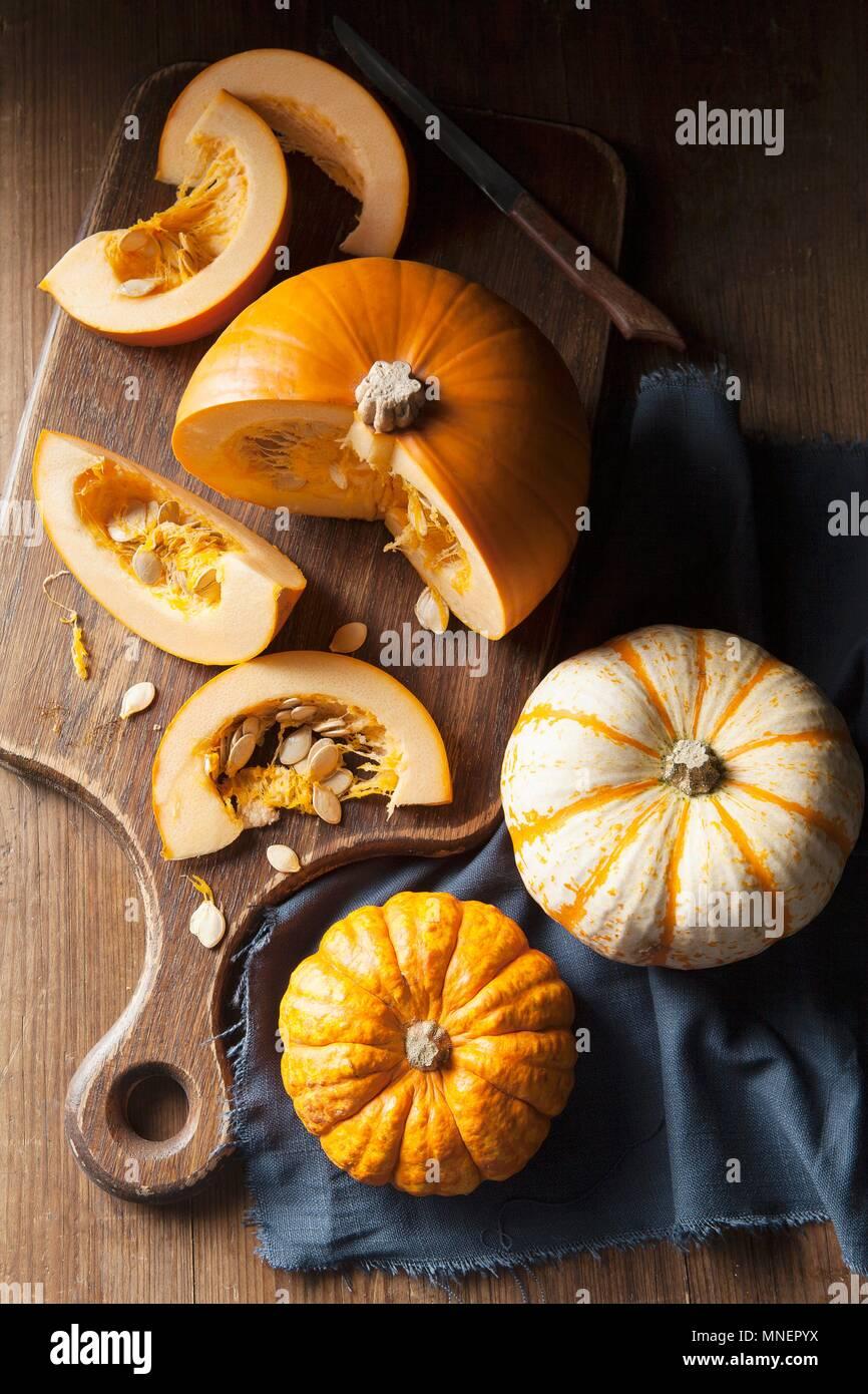 A piece of pumpkin on a wooden chopping board and munchkin pumpkins on a blue linen napkin - Stock Image