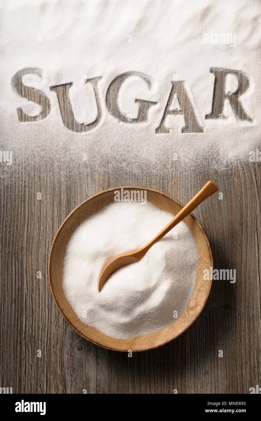 Sugar in a wooden bowl and spilled on a wooden background with the word 'sugar' - Stock Image