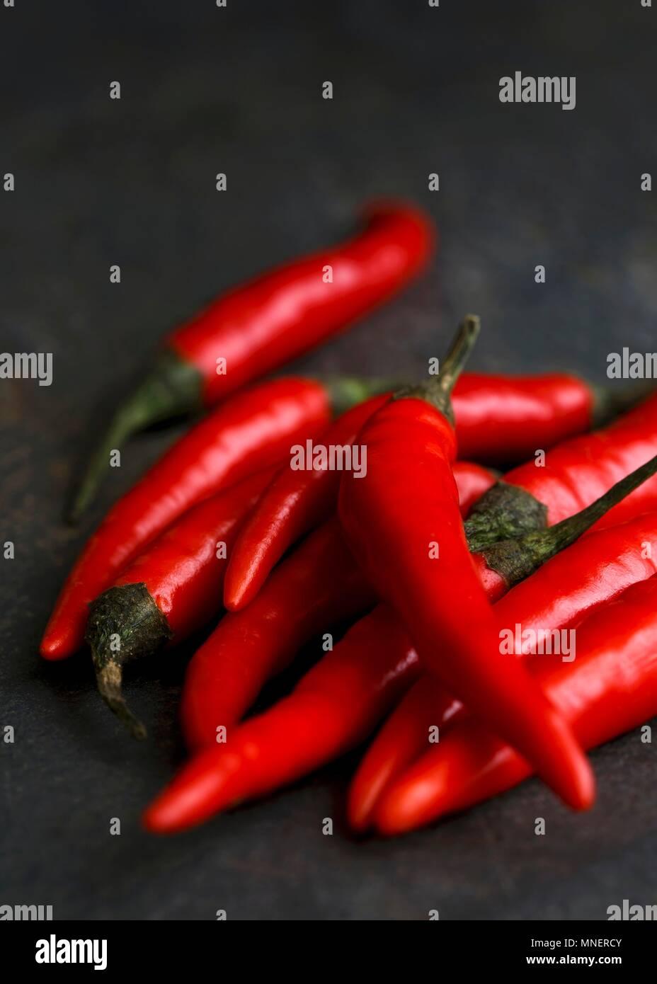 Whole fresh birds eye chillies on dark slate background - Stock Image