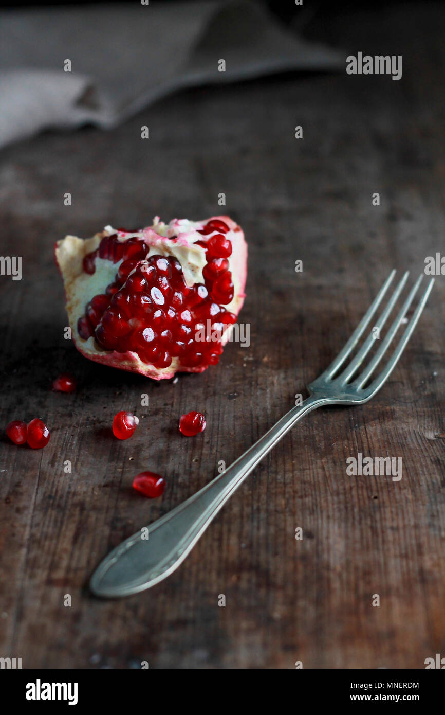 A piece of pomegranate with a fork on a wooden surface - Stock Image