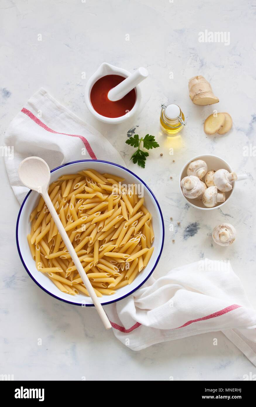 Ingredients for a pasta dish: penne, mushrooms, sieved tomatoes, olive oil and Ginger - Stock Image
