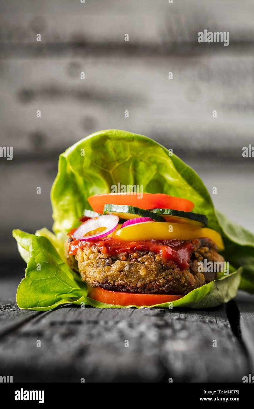 A gluten-free veggie burger in a lettuce leaf - Stock Image