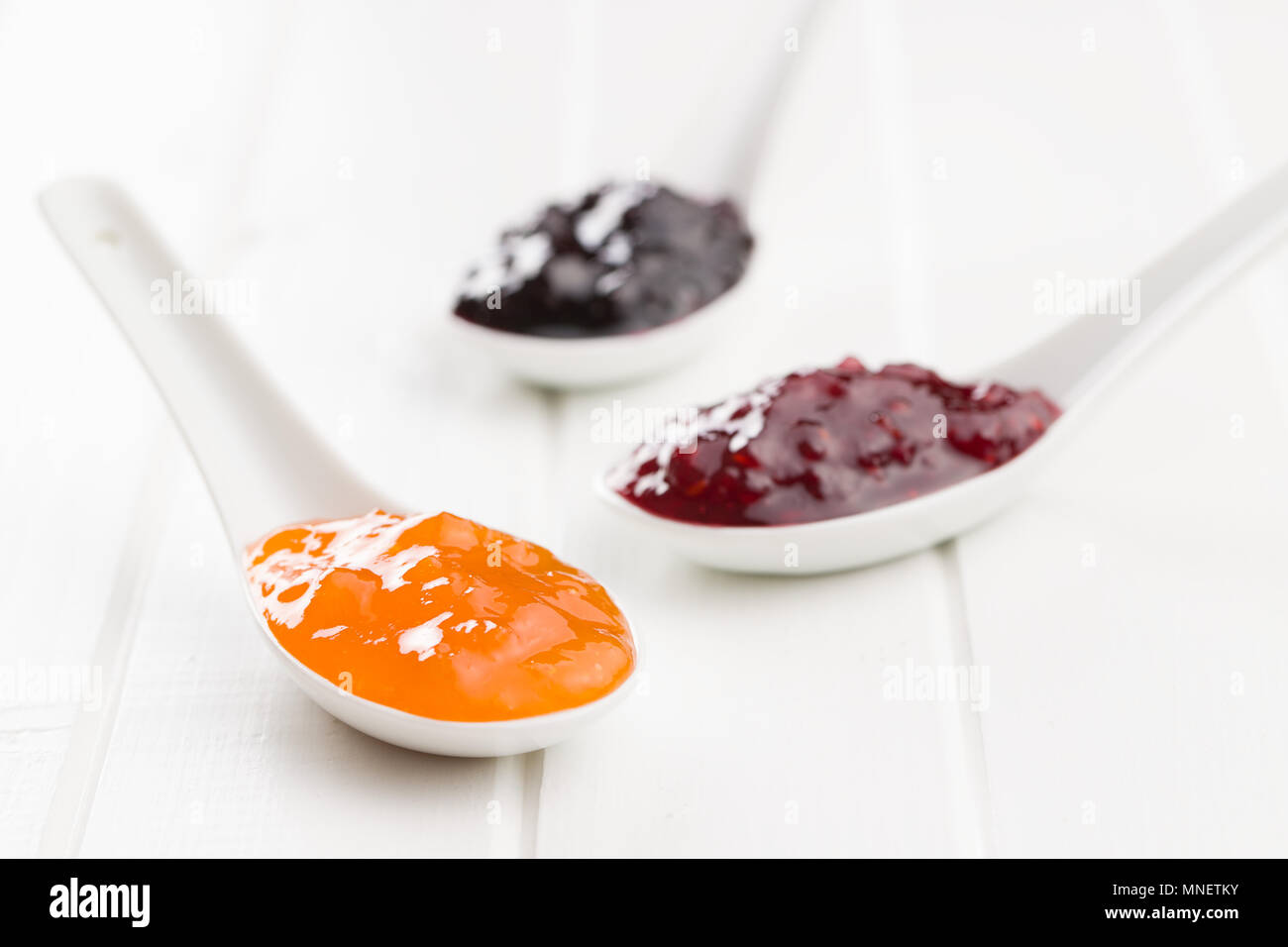Tasty fruity jam in ceramic spoon. - Stock Image