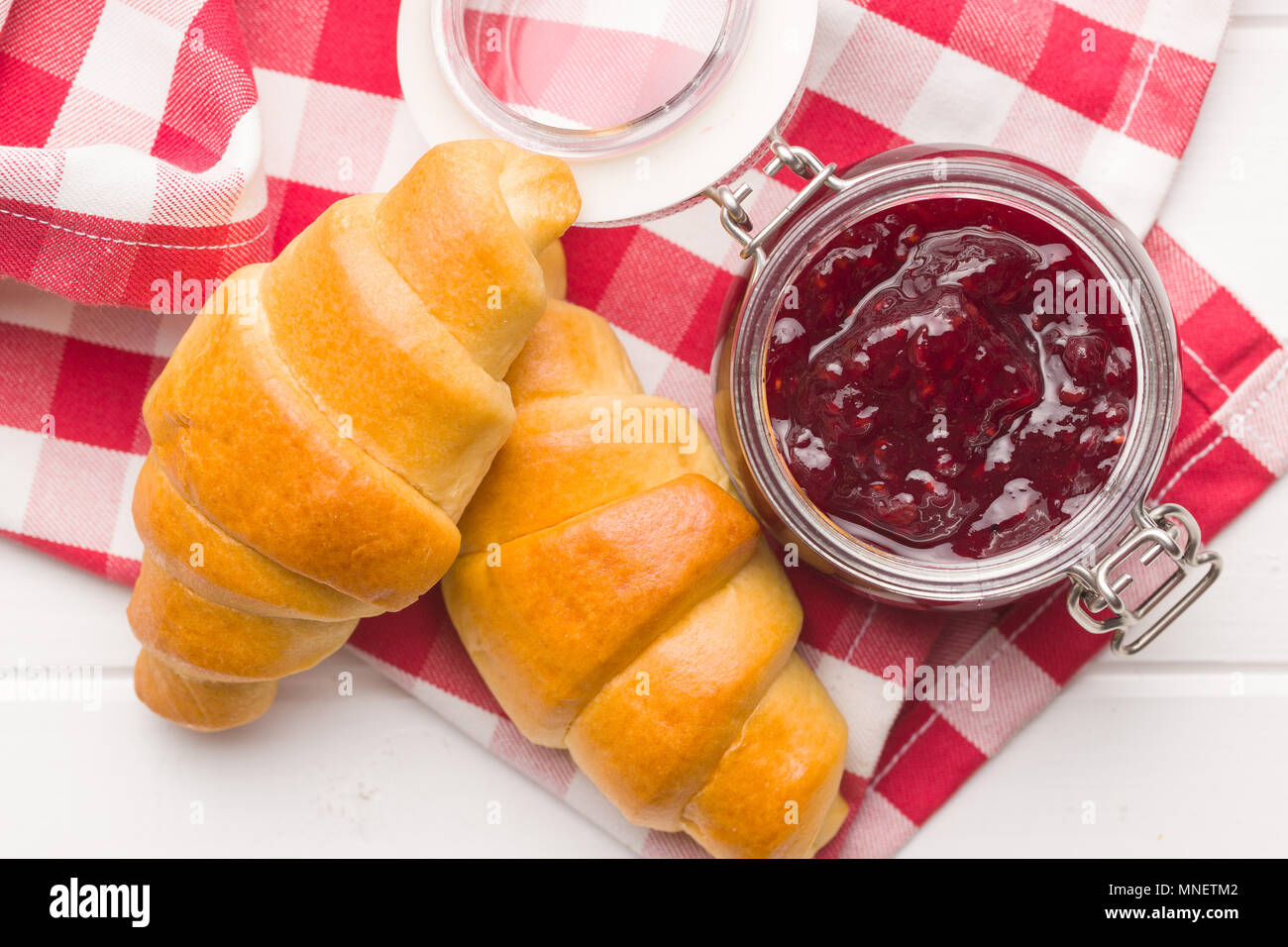 Sweet croissants and jam on checkered napkin. - Stock Image