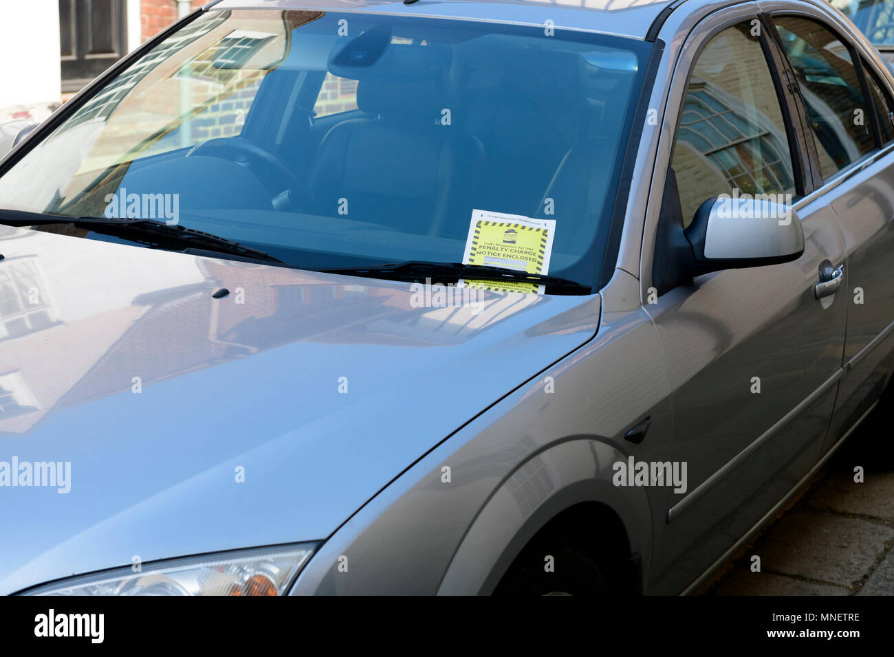 Parking penalty charge notice under car windshield wipers - Stock Image