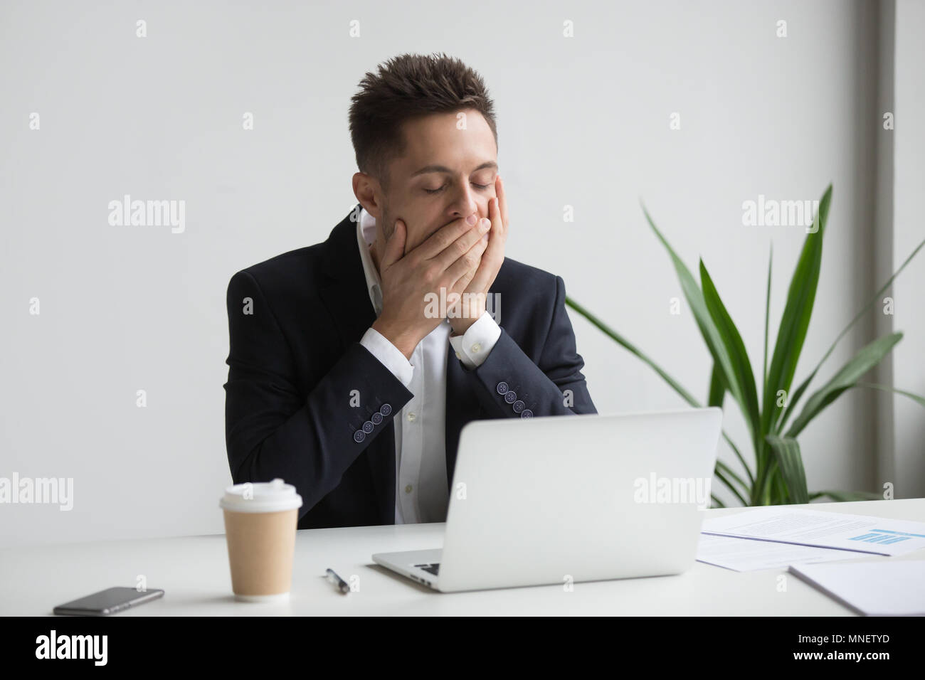 Tired office worker yawning working long hours - Stock Image