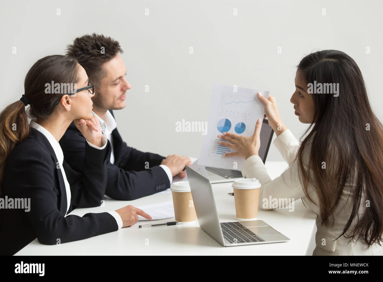 Female worker presenting visual templates to coworkers - Stock Image