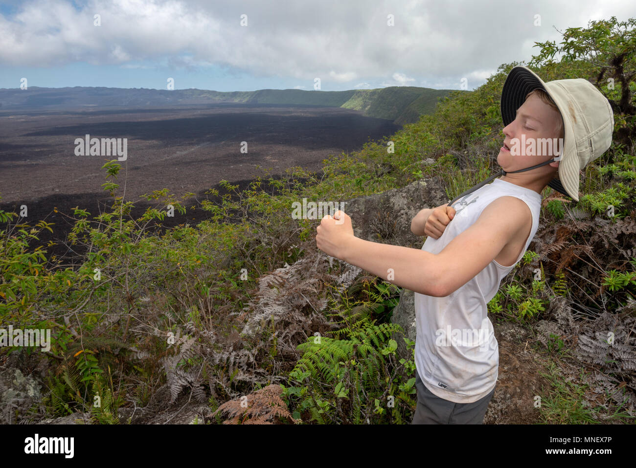 Boy playfully beating his chest on the rim of Sierra Negra Volcano, Galapagos Islands, Ecuador. - Stock Image