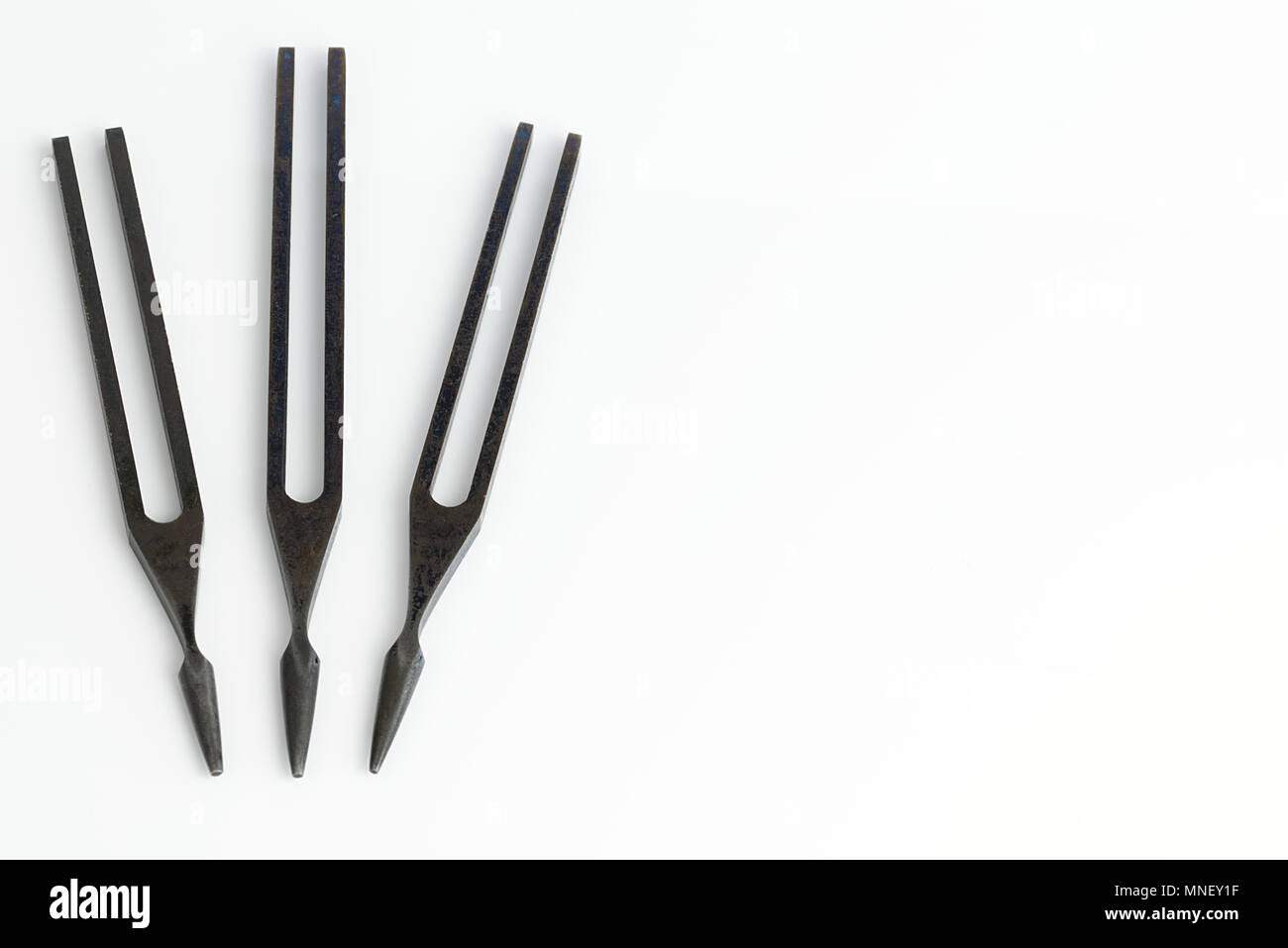 Three 3 tuning forks isolated on a white background. Science and Music concept - Stock Image