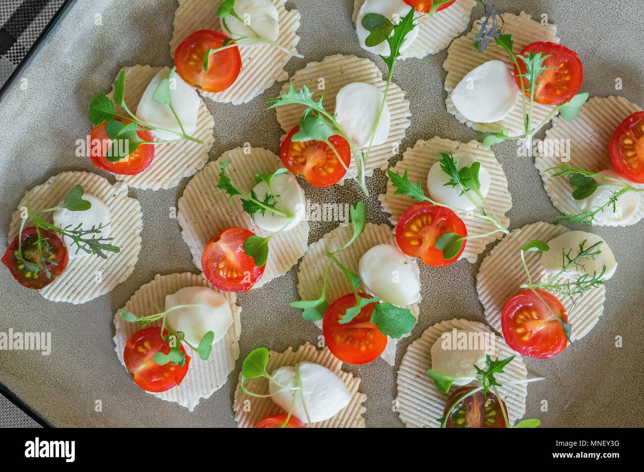 Mozzarella and tomatoes with thyme, arugula and Basil are on corn chips. Preparation of canapes. Close up. The view from the top - Stock Image