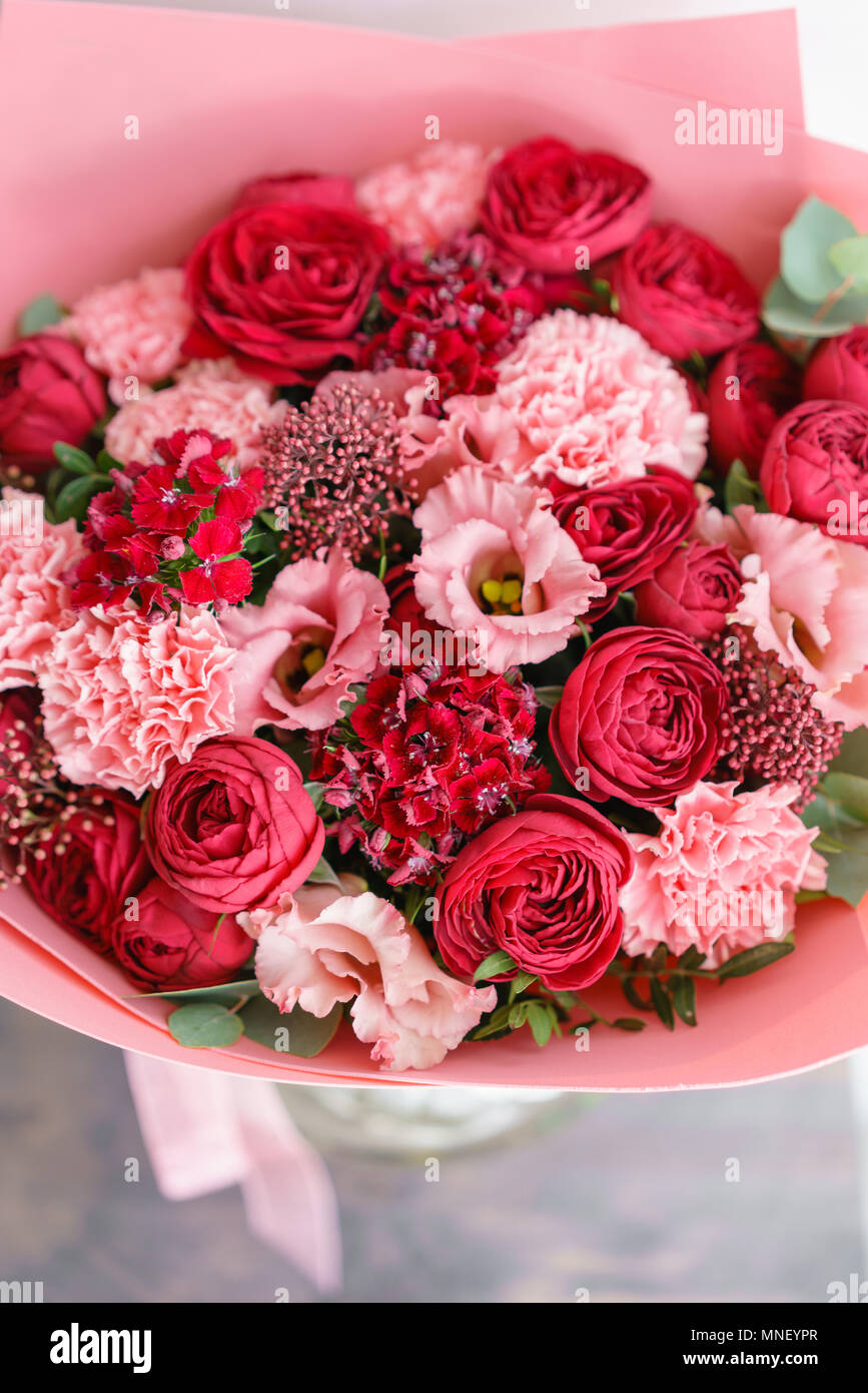 Bright red bouquet of beautiful flowers on wooden table. Floristry ...