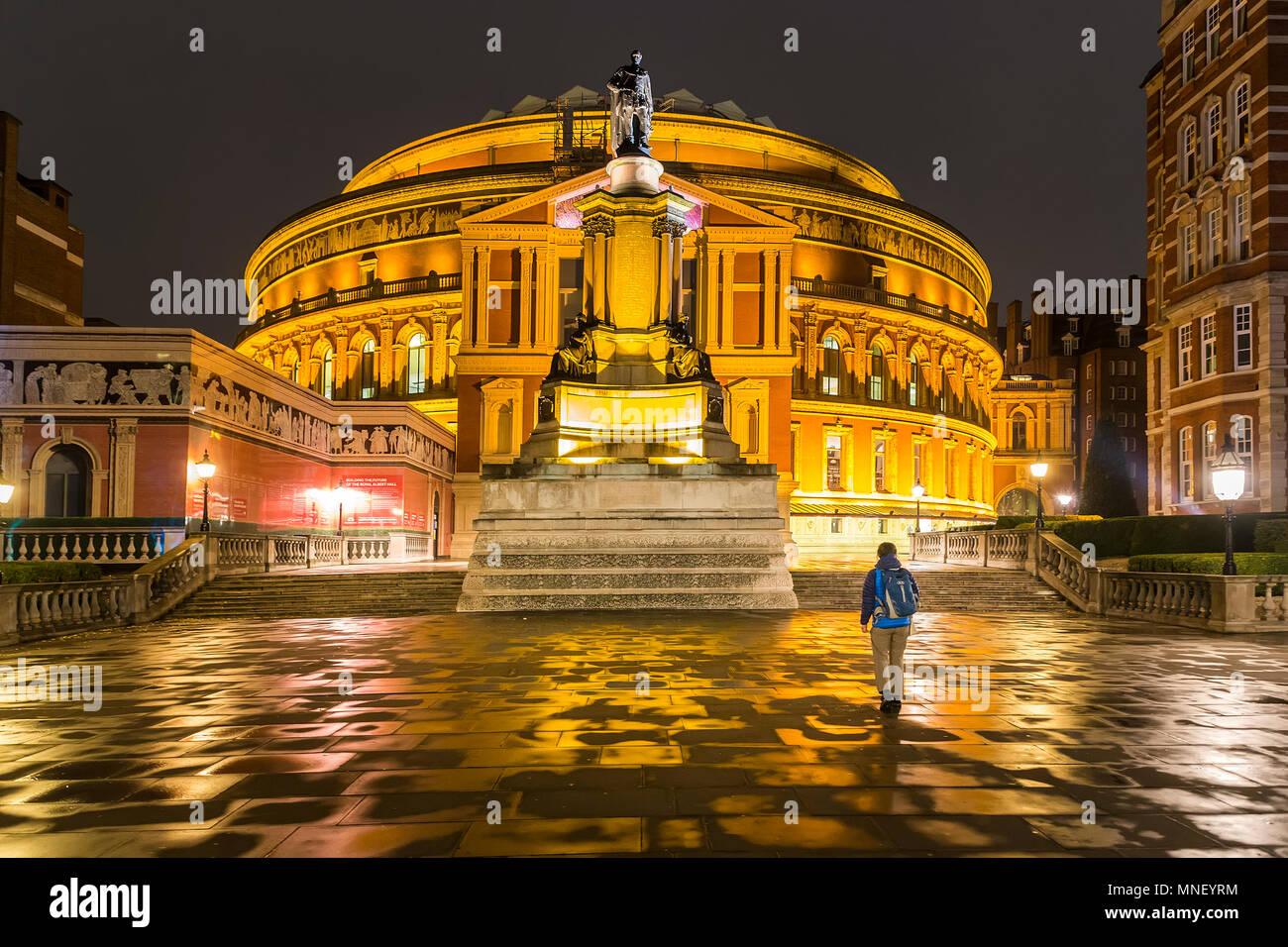 Person walking towards Royal Albert Hall at night, London, UK - Stock Image