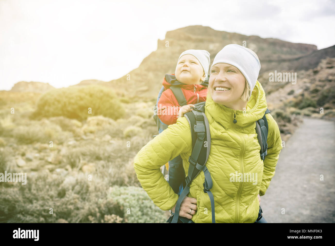 Super mom with baby boy travelling in backpack. Mother on hiking adventure with child, family trip in mountains. Vacations journey with infant carried - Stock Image
