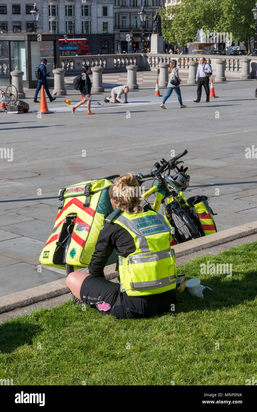 a cycle paramedic from the london ambulance metropolitan service sitting on the grass outside of the national gallery in trafalgar square in london. - Stock Image