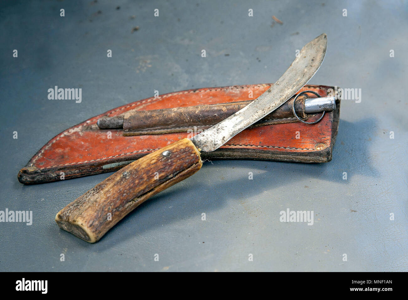 Worn butchers knife with a steel sharpener and a leather pouch - Stock Image