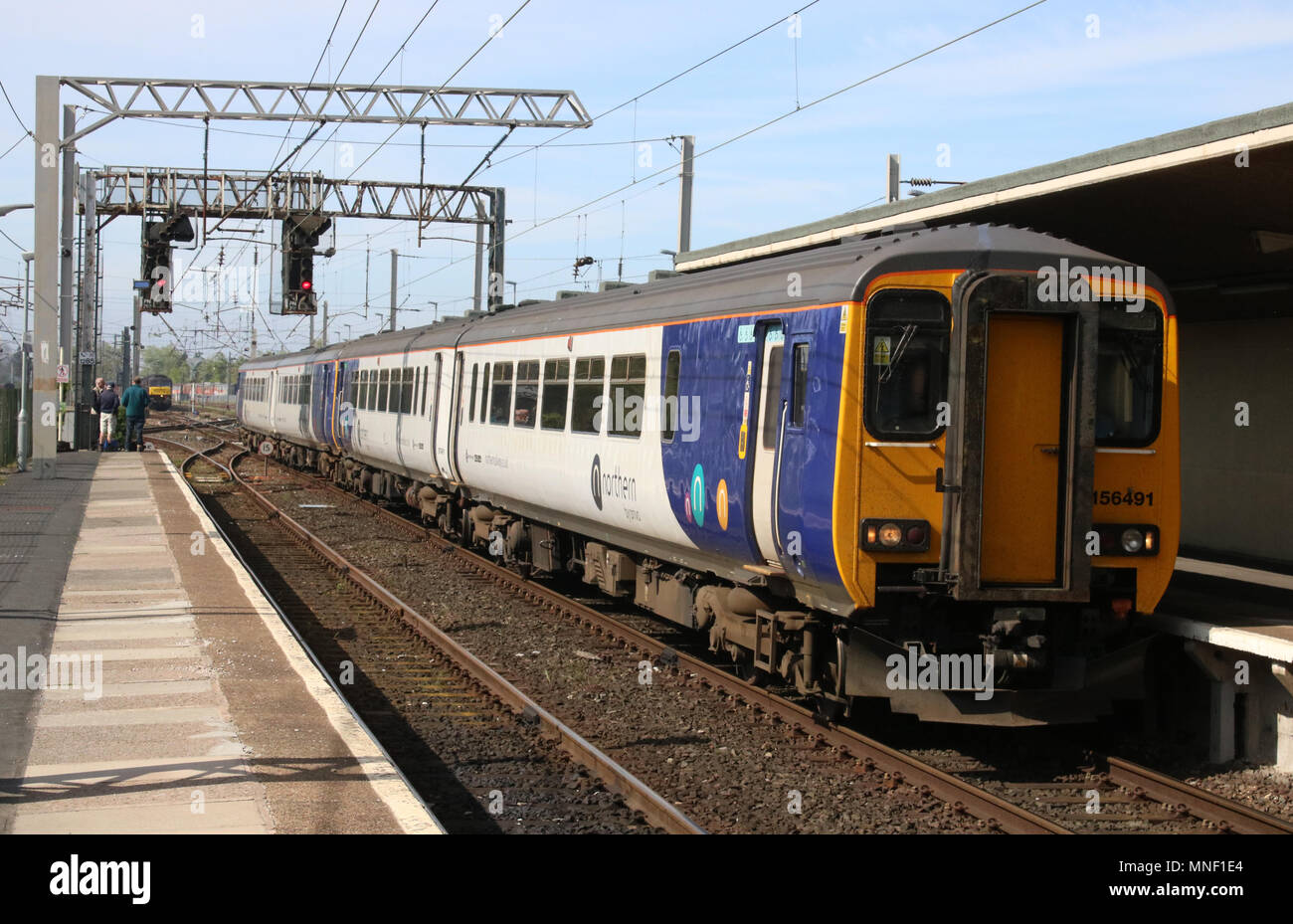 Two class 156 diesel multiple units in Northern livery entering Carnforth railway station platform 2 with a passenger train to Barrow-in-Furness. - Stock Image