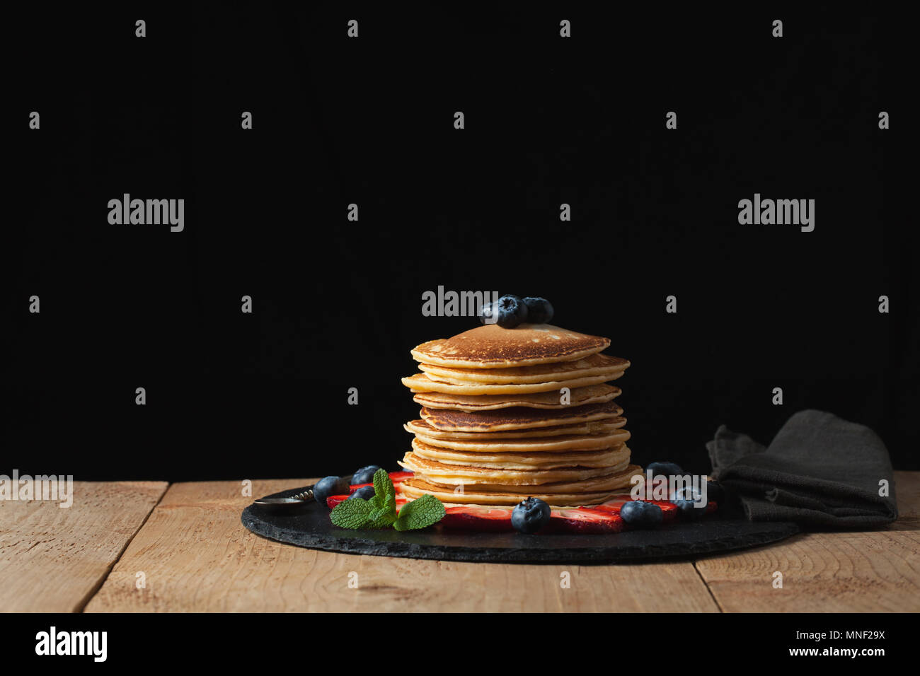 Front view of Stack of homemade plain pancakes with strawberries, blueberries and maple syrup served on black plate on black background with selective focus. With copy space - Stock Image