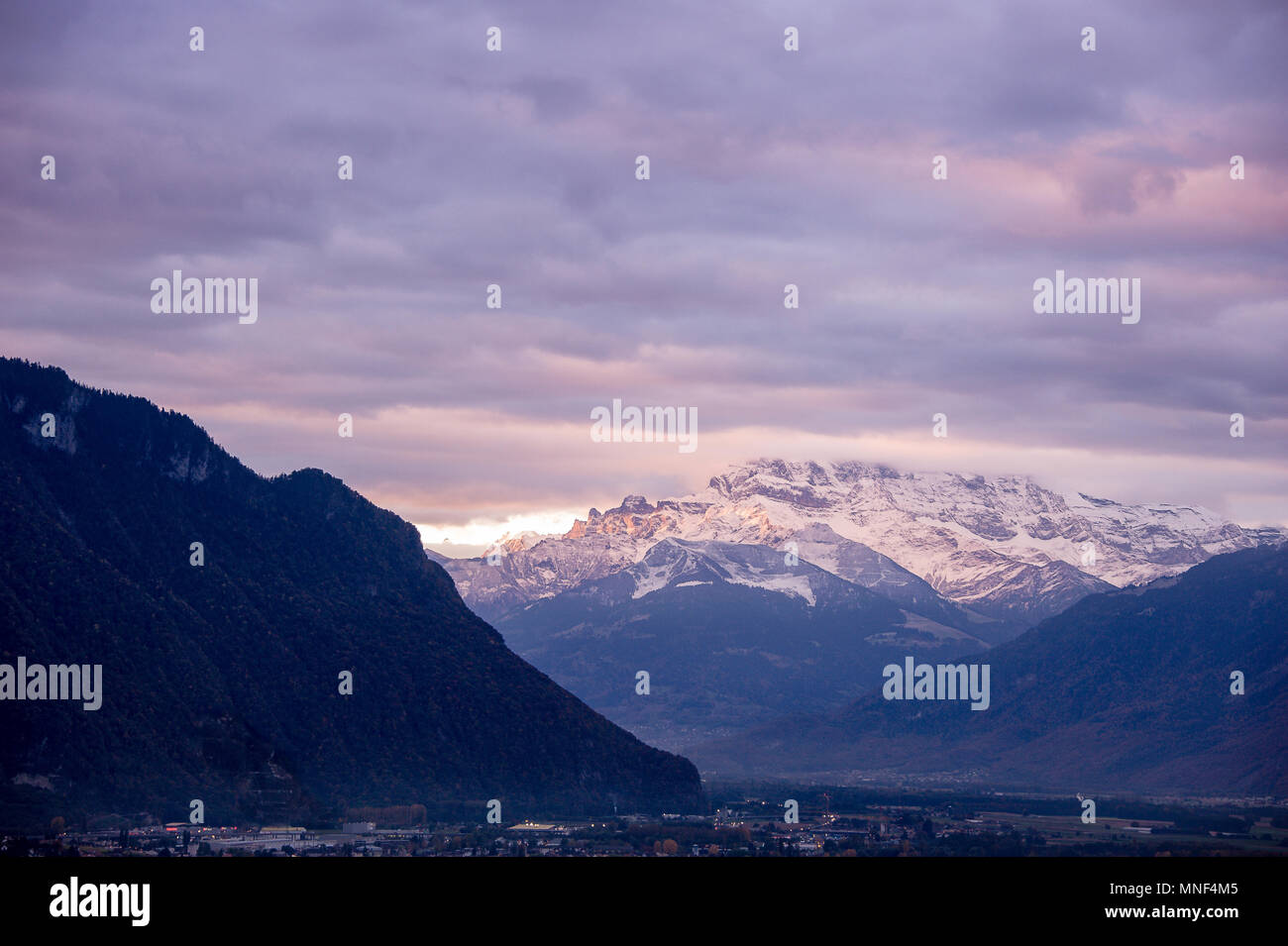 Panoramic view to the Dents du Midi (teeth of noon),  near Chablais, Switzerland. Dawn sunlight illuminates distant, snow covered peaks. Viewed from t - Stock Image
