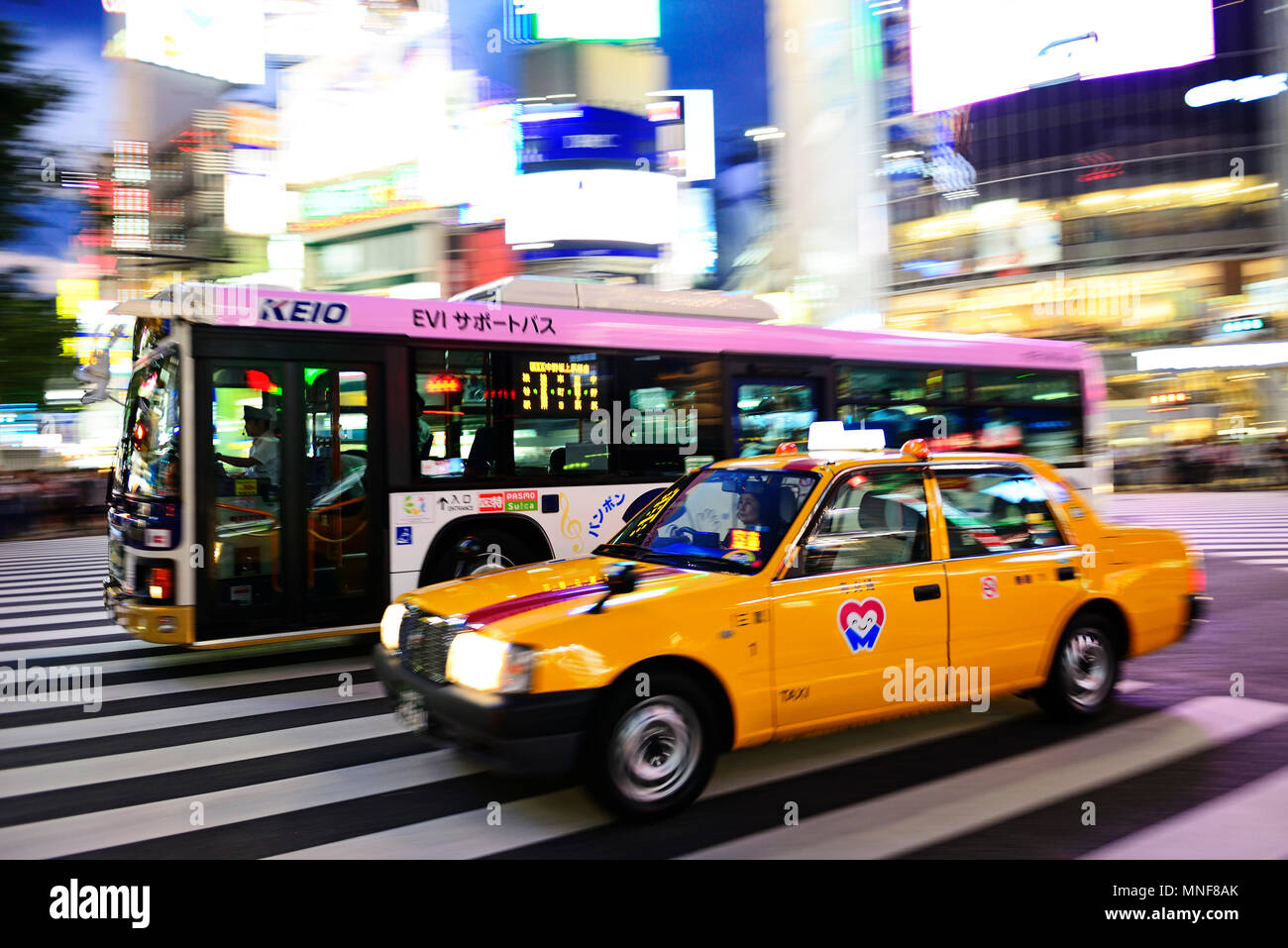 Infrastructure, traffic, yellow taxi and bus on Meiji Dori-Street, Shibuja Crossing, Tokyo, Japan Stock Photo