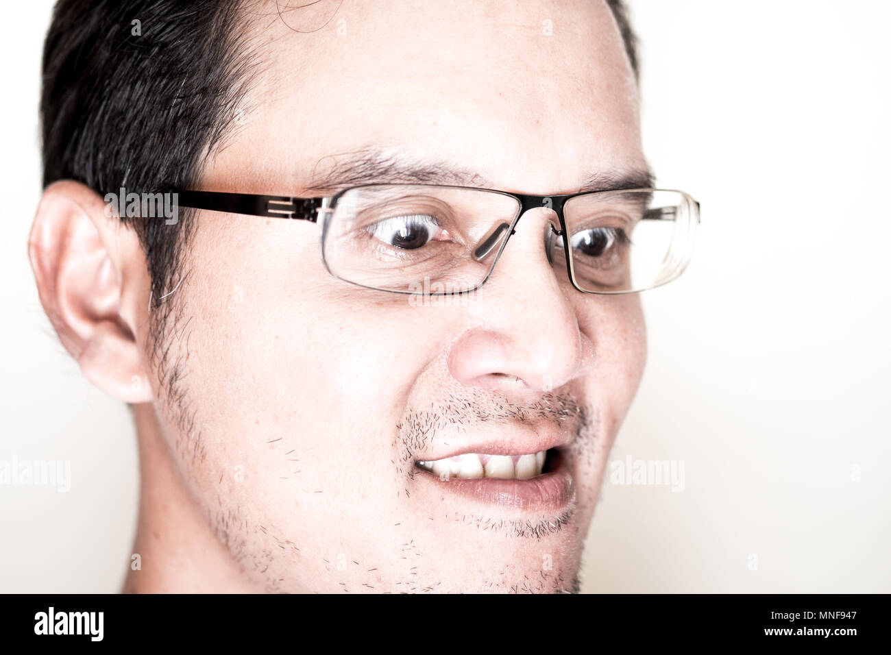 Face of Asian man with eyeglasses for near sighted feeling very angry and mad. His eyes is wided open and gritting his teeth. - Stock Image