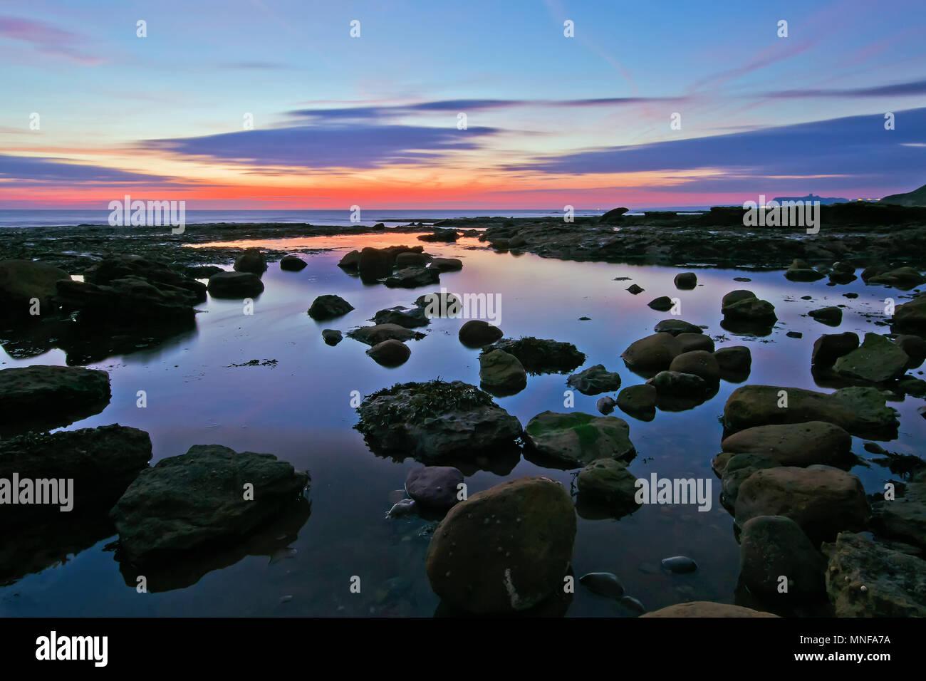 Coastal rock pools reflect the brilliant hues of dawn before sunrise at Crook Ness, near Scarborough. - Stock Image