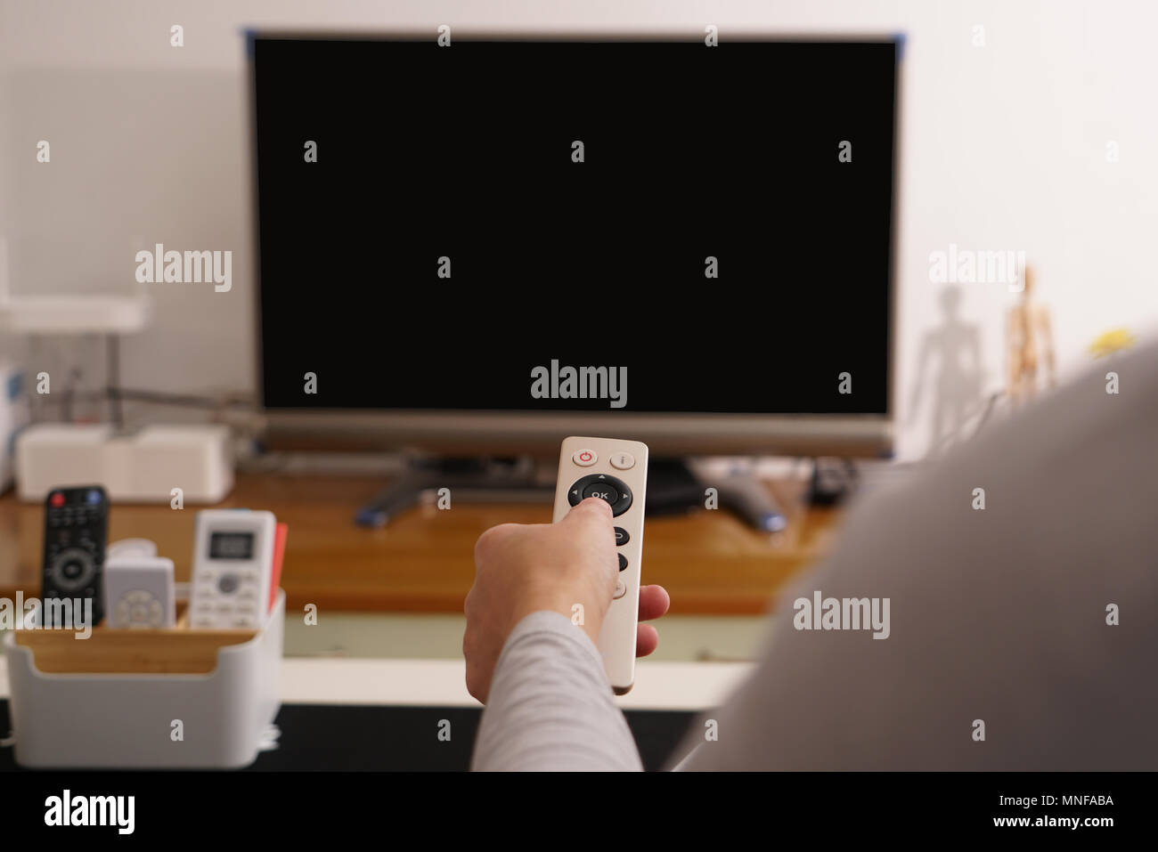 a women hand hold the remote control of the TV box in the living room 3d97e2514d