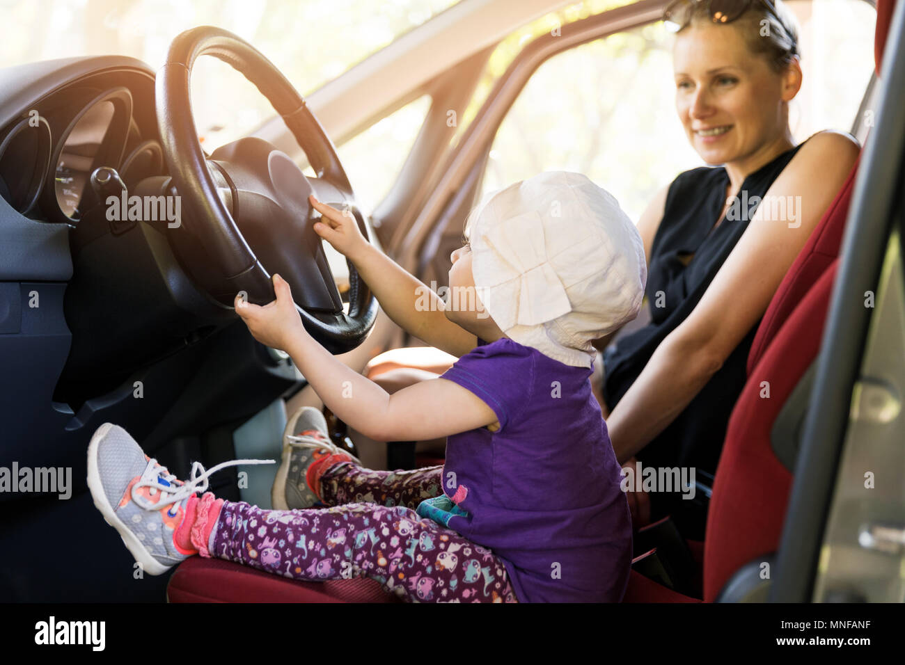 Mother With Child Playing In The Car Steering Wheel