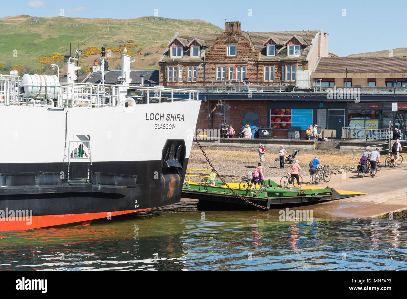 cyclists disembarking Loch Shira ferry in Largs, Scotland returning from Millport Great Cumbrae - Stock Image