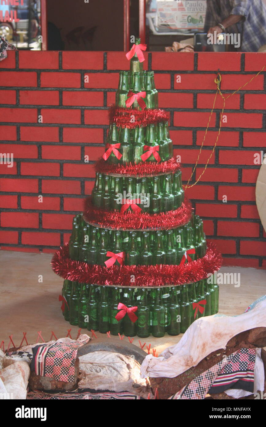 Christmas Tree Made From Green Bottles with Red Tinsel and Red Bows, Colva, India - Stock Image