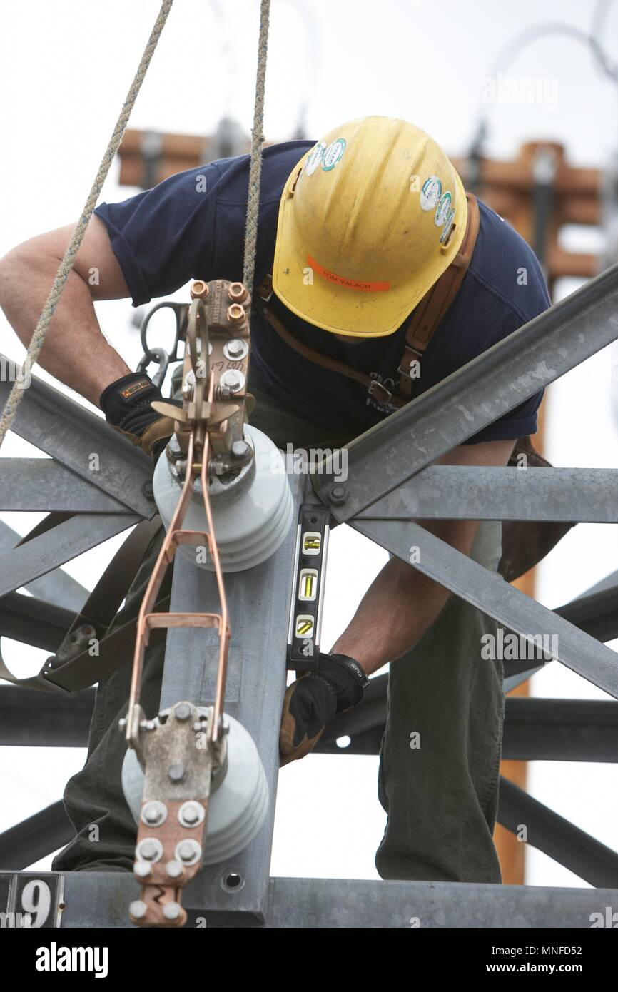 Lineman Installing New Line to Accommodate Solar Panel Farm Improving the Electrical Grid - Stock Image