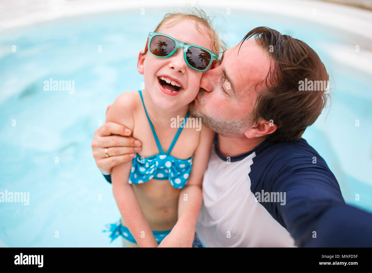 Happy family father and his adorable little daughter at outdoors swimming pool making selfie - Stock Image