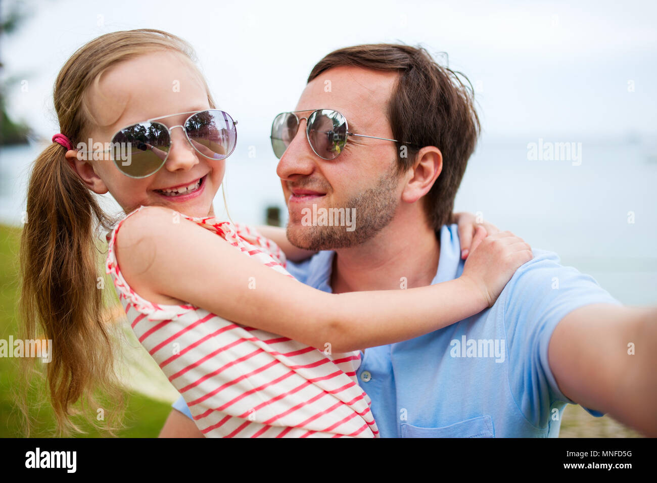 Happy family father and his adorable little daughter at beach making selfie - Stock Image