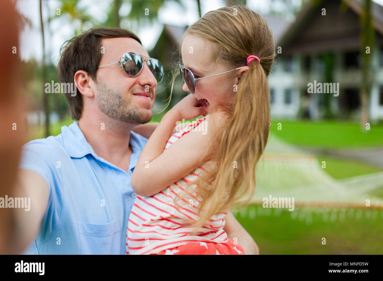 Happy family father and his adorable little daughter on vacation taking selfie - Stock Image