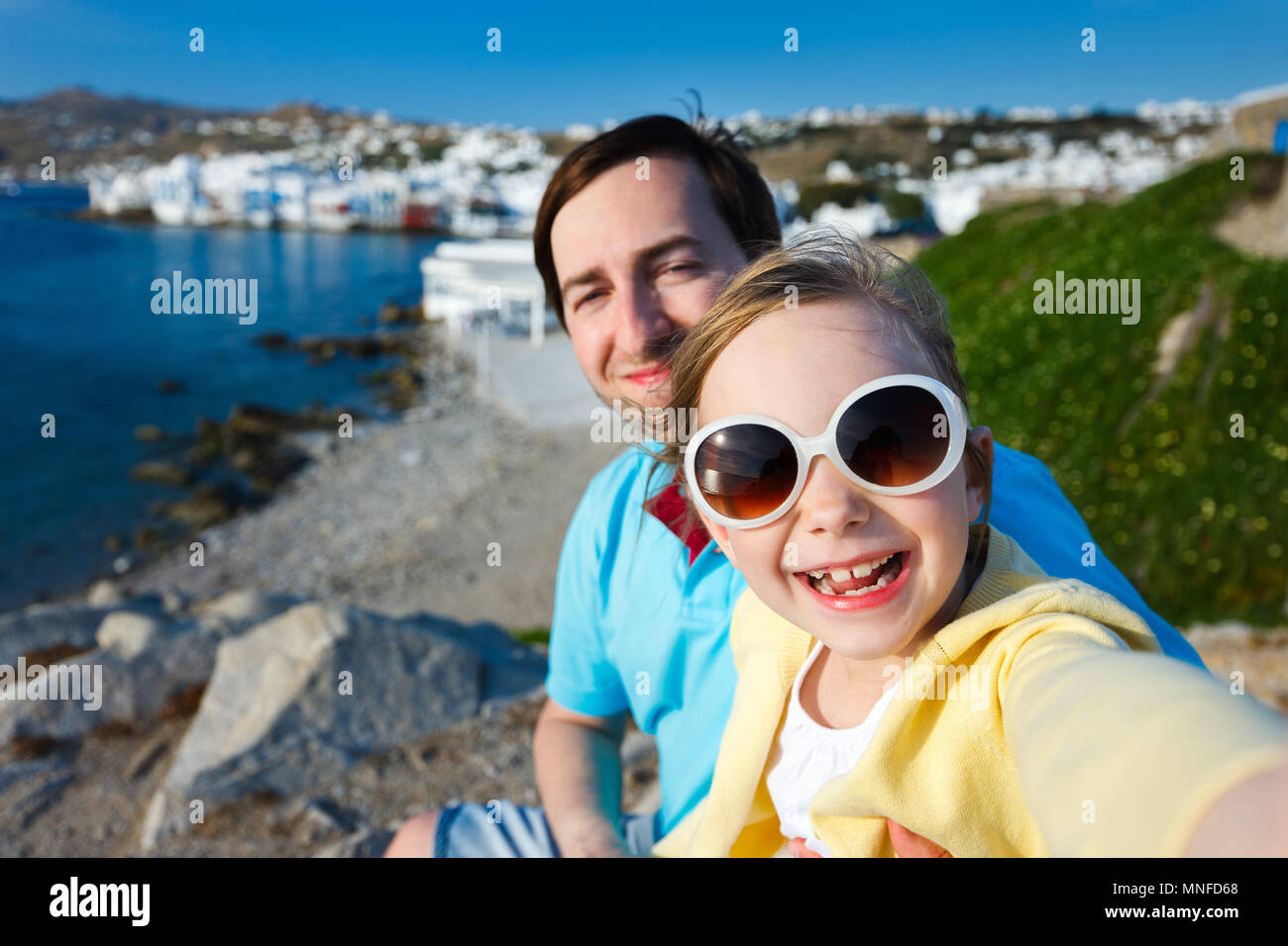 Happy family father and his adorable little daughter on vacation taking selfie at Little Venice area on Mykonos island, Greece - Stock Image