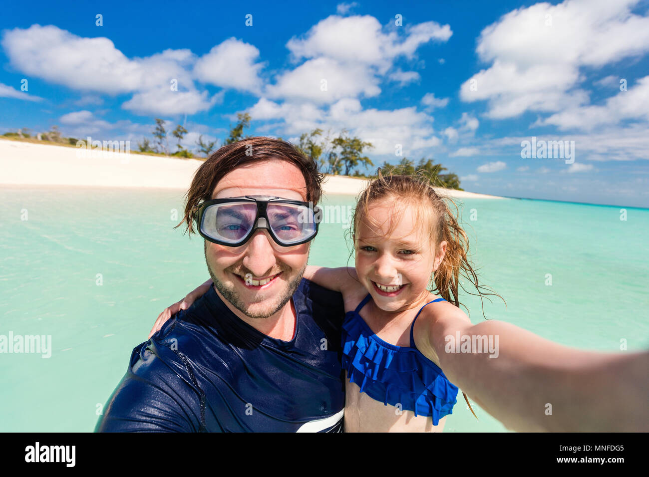 Happy family father and his adorable little daughter at beach taking selfie - Stock Image