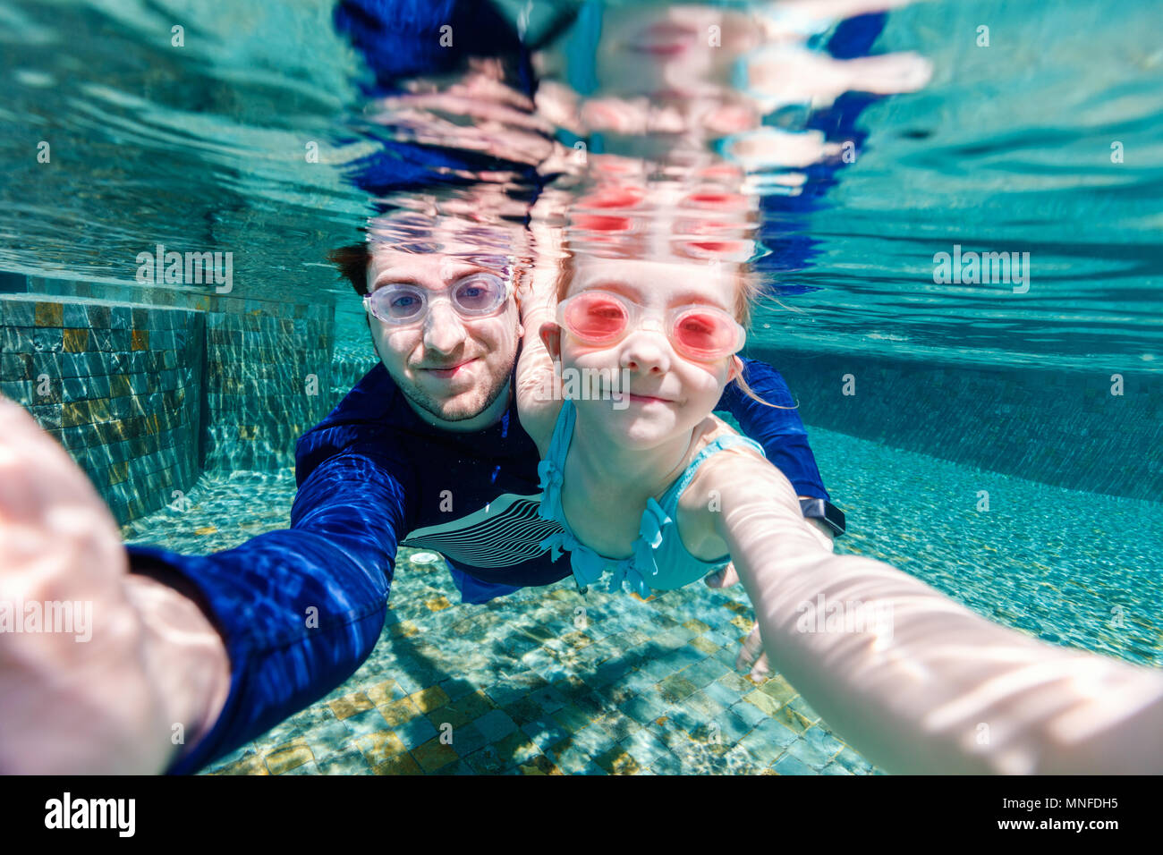 Family father and daughter swimming underwater and making selfie - Stock Image